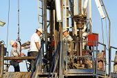 stock photo of oil drilling rig  - Roustabouts work on lower platform of oil drilling rig Kern County California - JPG
