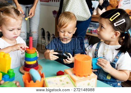 Nursery children playing with teacher