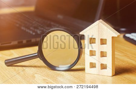 Wooden House And Magnifying Glass