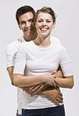 An attractive young couple posing.  They are wearing white. The male has his arms wrapped around the female.  They are smiling happily at the camera. Vertically framed photo.
