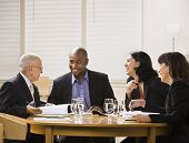 A group of business people are in a meeting in an office.  They are talking and laughing and looking