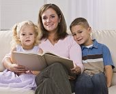 A mother is reading to her two young children.  They are all smiling at the camera.  Square framed s