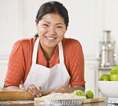Asian woman rolling dough, making pie, smiling at camera with flour on her face. Square.