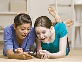 Teenage girls text messaging on cell phone