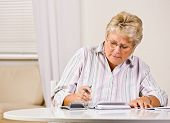 Senior woman writing checks