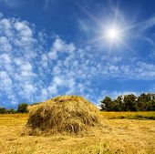 Haystack and sun in  blue sky