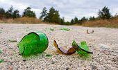 Partes da garrafa de vidro quebrado na estrada