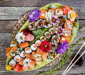 Sushi Set Nigiri And Sushi Rolls Decorated With Flowers On Bamboo Background. Japanese Cuisine. Top  poster