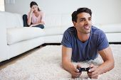 Man playing video games while his girlfriend is getting mad at him in their living room
