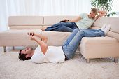 Woman watching television while her boyfriend is using his cellphone in their living room