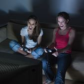 stock photo of video game  - pictures in a living room of two young girls sitting on a couch playing video game - JPG