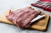 Sliced Beef Tongue Slices On Wooden Board. poster