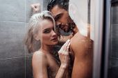 Naked Couple Embracing In Passion And Taking Shower Together poster