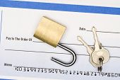 A lock on a blank check insinuating one should keep a close watch on their checking account and fina