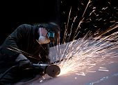 Worker cutting metal using rotary disc