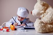 Humorous Photo. Little Cute Child Girl Playing Doctor Fills Up The Prescription Form To The Patient. poster