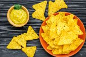 Snack For Party. Mexican Nachos Near Guacamole Sause On Black Background Top View poster