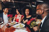 Friends In A Restaurant Enjoying Romantic Evening. Group Happy Friends Enjoying Dating In Restaurant poster