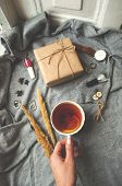 Winter Cozy Concept. Gray Knitted Sweater, Cup Of Tea, Giftbox And Watches On Grey Background. poster
