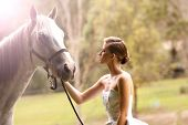 beautiful young woman with a grey horse in the country