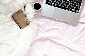 Home Office In Bed With Laptop And Mug Of Coffee, Pen, Kraft Notepad On A Pink Linens And White Fluf poster