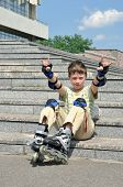 The jolly boy with roller blades sitting at the steps