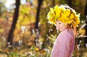 Beautiful Little Girl In A Wreath Of Maple Leaves In Autumn Forest