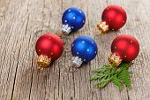 Christmas balls on wooden background with green thuja branch