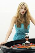 Young blond woman standing at roulette wheel