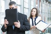 picture of embarrassing  - Businessman hides from coworker behind folder - JPG