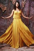 beautiful young brunette woman wearing yellow evening dress