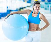 Happy woman at the gym holding a Pilates ball