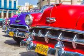 HAVANA-JUNE 21:Colorful row of vintage american cars on June 21, 2013 in Havana.These classic cars are a worldwide famous sight and a tourist attraction of the island