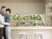 Profile shot of man and woman embracing in kitchen
