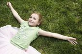 High angle view of smiling young girl with arms outstretched lying on grass