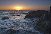 stock photo of marblehead  - The sun just breaks over the horizon on a rocky beach - JPG