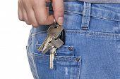 a mão de uma jovem mulher em jeans com chaveiro. chaves para o carro e casa