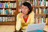 Schüler - junge Frau in Bibliothek mit Laptop lernen, sie konzentriert