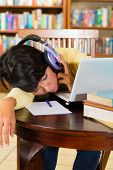 Student - Young woman in library with laptop learning, she is exhausted and asleep