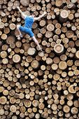 stock photo of encounter  - Fit climber going down the large pile of cut wooden logs - JPG