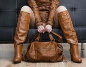 stock photo of leggins  - detail of sitting woman in brown clothes holding a handbag - JPG