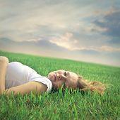 hermosa chica rubia tumbado en la hierba