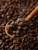 Coffee beans in wooden spoon with smoke, close up