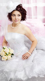 foto of glans  - Portrait of young brunette bride with a bouquet on pink - JPG