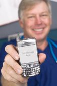 stock photo of inference  - A doctor displays his cell phone as if showing someone the screen display - JPG
