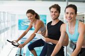 Fit women in a spin class with trainer taking notes and smiling at camera at the gym