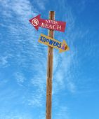 image of nudism  - wooden arrow direction signs post to the nude beach and showers against a blue sky - JPG