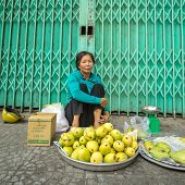 HO CHI MINH CITY, VIETNAM - MARCH 26: Unidentified old woman selling mangoes on the sidewalk in Ho C