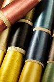 stock photo of rayon  - close up of bobbins of colorful silk thread - JPG