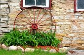 pic of wagon wheel  - An old antique red metal wagon wheel is leaning up agains a stone barn on a rustic farm - JPG